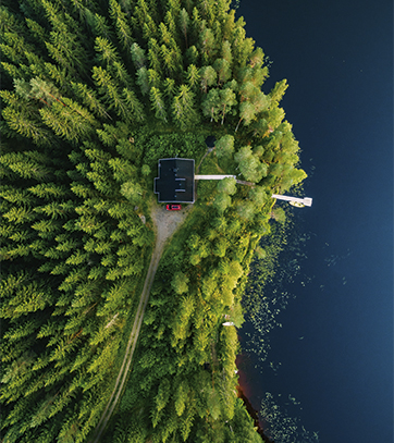 Aerial view of wooden cottage in green forest by the blue lake i